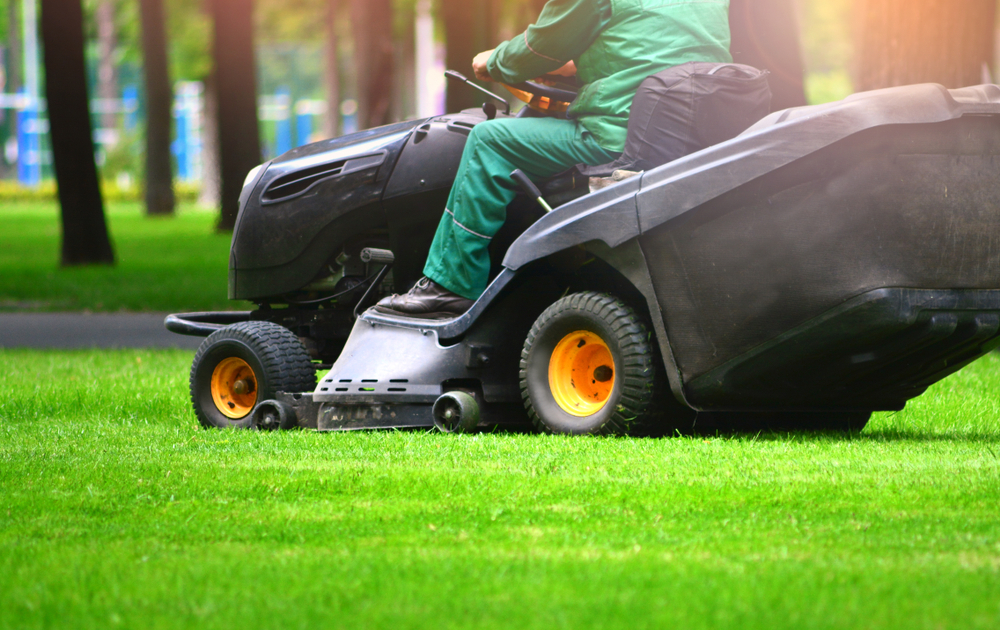 man mowing on tractor
