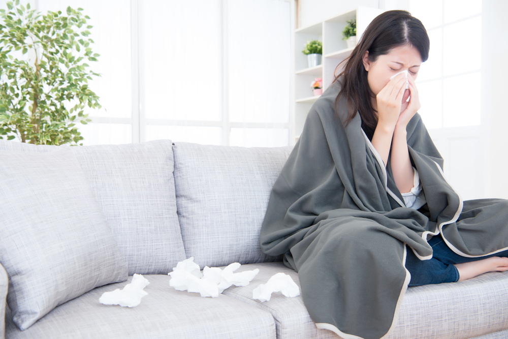 woman with a cold sitting on a couch