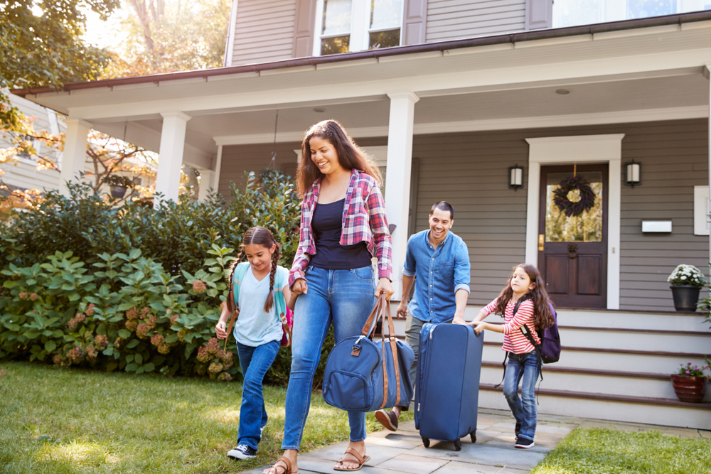 family leaving home with luggage for vacation